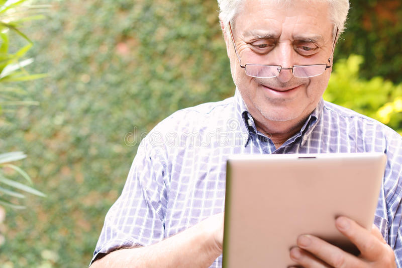 Stary człowiek używa cyfrową pastylkę obraz stock