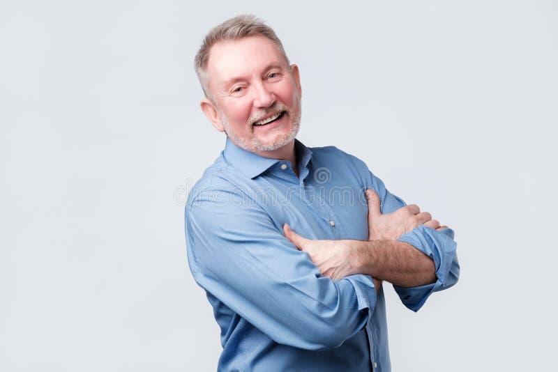 Stary człowiek w błękitnych koszulowych falcowanie rękach, patrzeje oddalony i uśmiechnięty fotografia stock