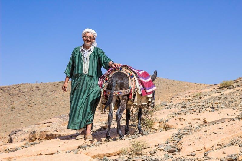 Stary człowiek w krajowym marokańczyku odziewa Przewdonik z osłem obraz stock