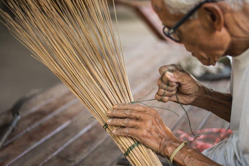 Stary człowiek wiązał arkanę robić miotle od kokosowych gałąź zdjęcia royalty free