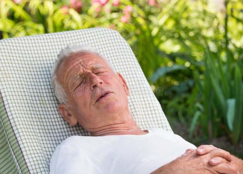 Stary człowiek z bólem w ogródzie fotografia stock