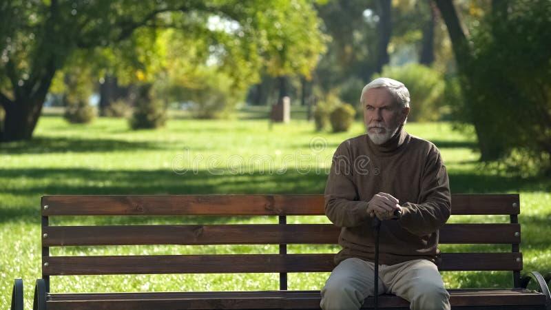 Stary człowiek z chodzącym trzciny obsiadaniem na ławce, odpoczywa po chodzić w parku obraz royalty free