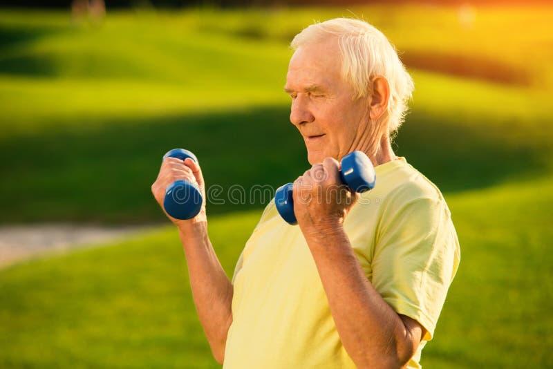 Stary człowiek z dumbbells zdjęcie royalty free