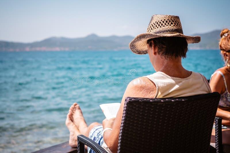 Stary człowiek z kapeluszem siedzi przy barem morzem, czyta książkę i cieszy się słońce w Zadar, fotografia royalty free