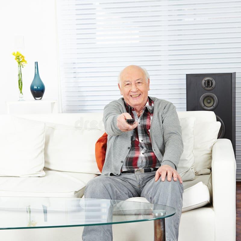 Stary człowiek z pilot do tv obraz stock