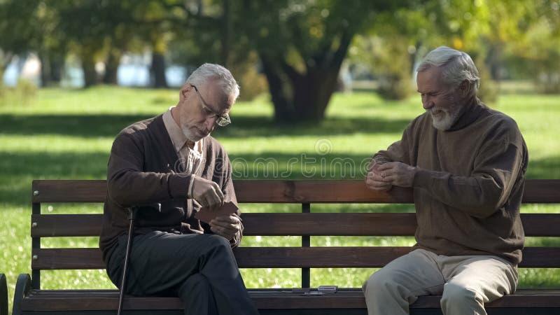 Stary cz?owiek karty do gry i mie? zabawa w miasto parku, aktywny styl ?ycia, emerytura obraz royalty free