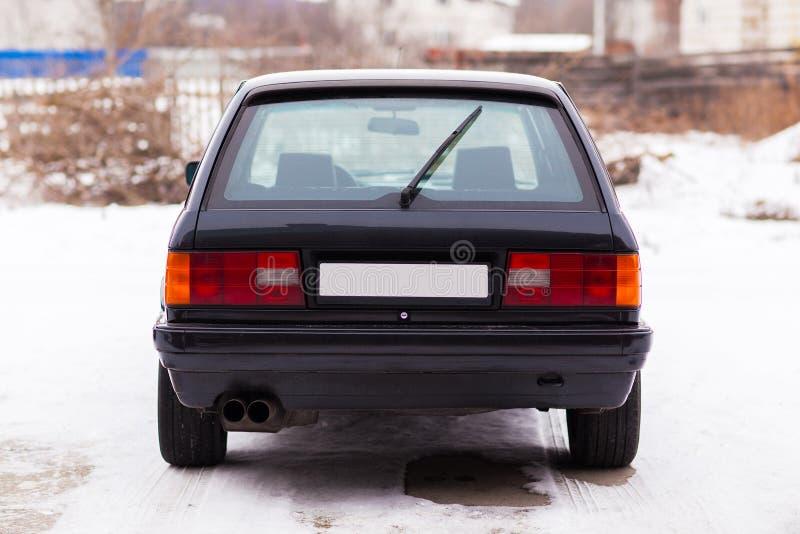 Stary, czarny, Niemiecki rodzinnego samochodu tylni widok w zimie, fotografia stock