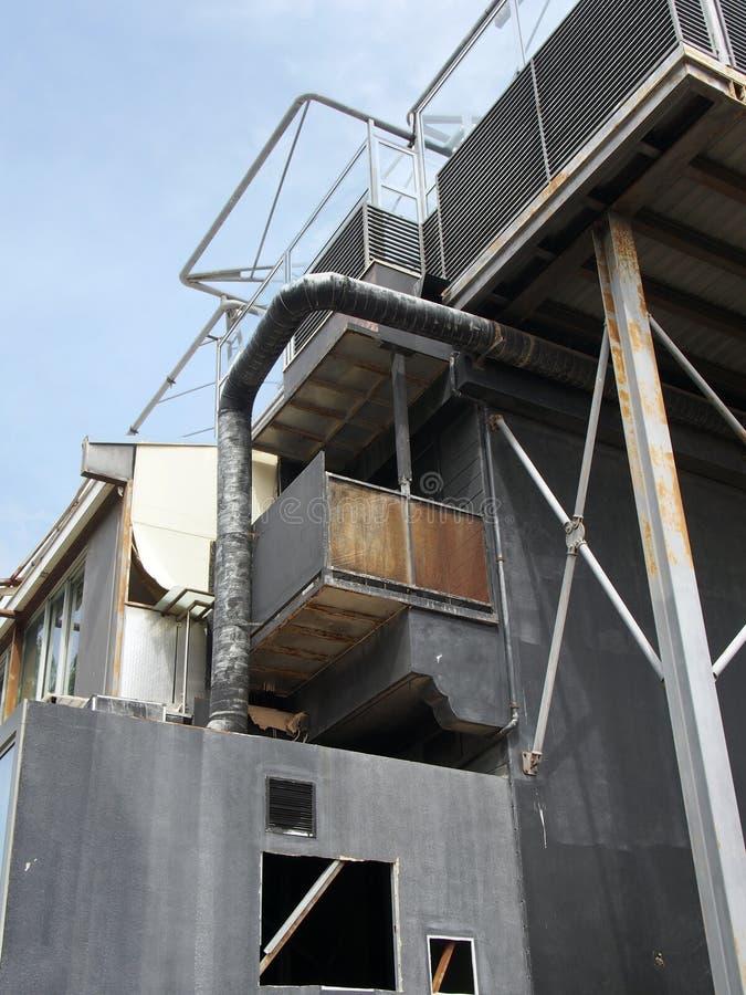 Stary czarny przemysłowy budynek z rdzewieć stalowych stropnica zbiorniki, drymby i poręcze przeciw niebieskiemu niebu zdjęcie stock
