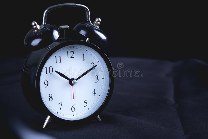 Stary Czarny rocznika budzik na czarnym bedspread zdjęcia royalty free