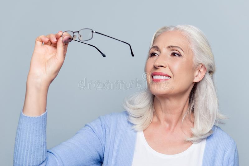 Stary, czarujący, ładna kobieta patrzeje przez eyeglasses, senior, zdjęcia stock