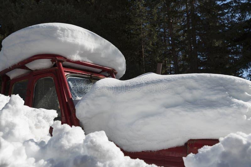 Stary czerwony ciągnik łapać w pułapkę pod snowdrift w w lesie Rodopi góra obrazy stock