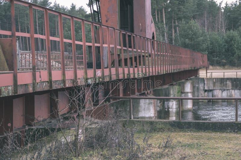 stary czerwony metalu most nad wodą - rocznika retro spojrzenie fotografia stock