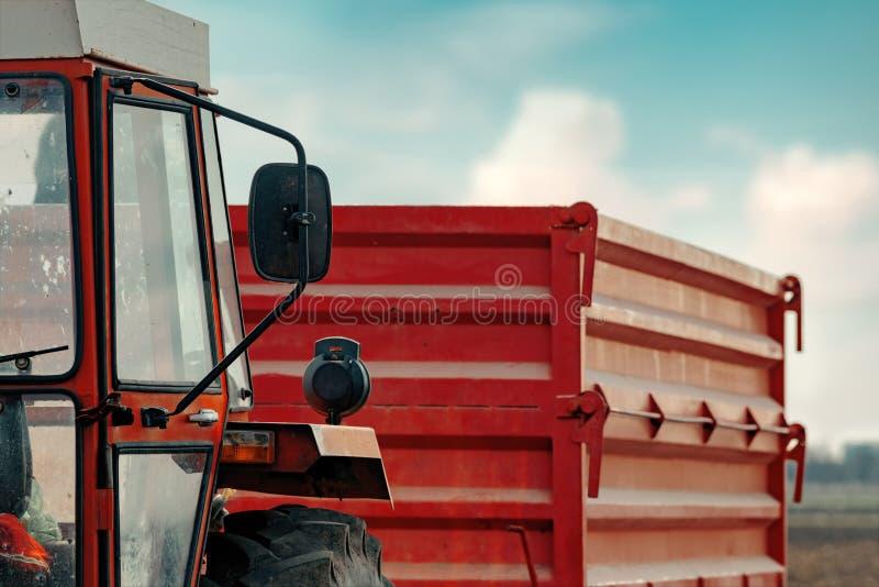 Stary czerwony rolniczy ci?gnik z przyczep? na brud wsi drodze zdjęcie stock