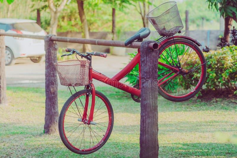 Stary czerwony rower wiesza na stalowym por?czu dekorowa? ogr fotografia stock
