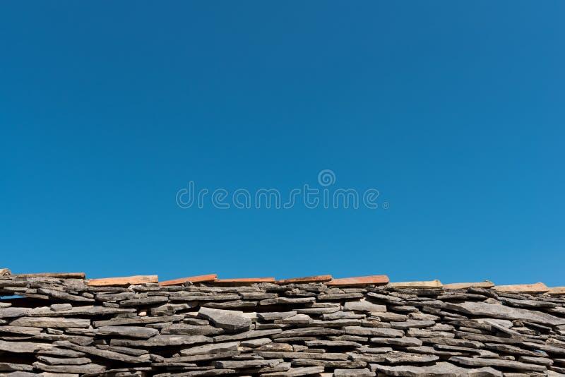 Stary dach z popielatymi kamień płytkami i jasnym niebieskim niebem w tle zdjęcia royalty free