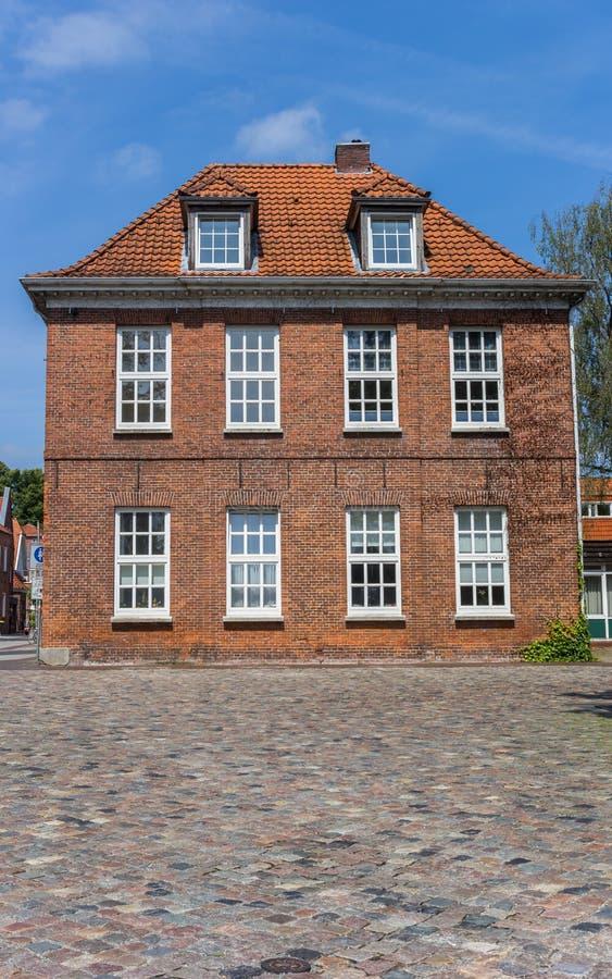 Stary dom przy cobblestoned ulicą w Aurich obrazy stock