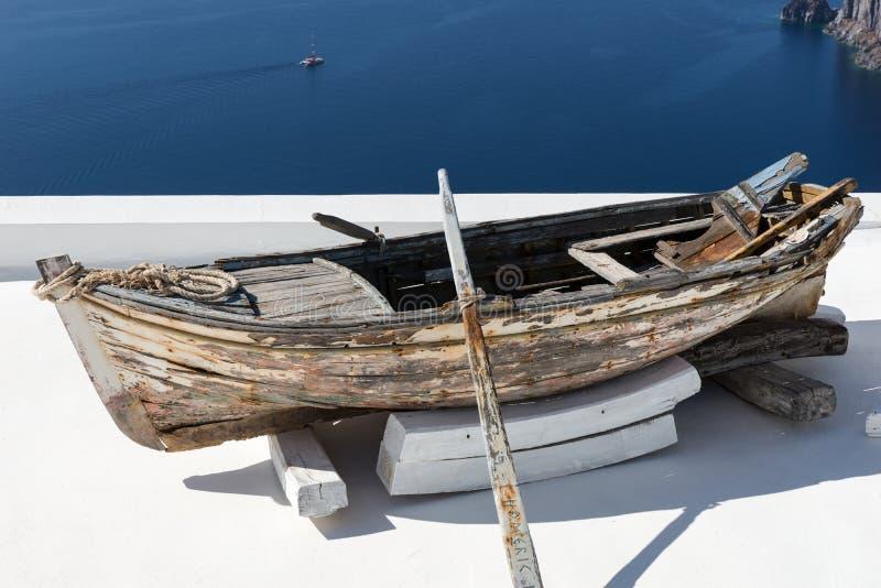 Stary drewniany łódkowaty odpoczywać na białym dachu Santorini obrazy royalty free