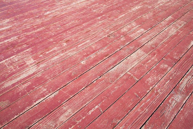 Stary drewniany czerwony podłogowy tekstury zbliżenie Diagonalne deski z obieranie gwoździami i farbą fotografia stock
