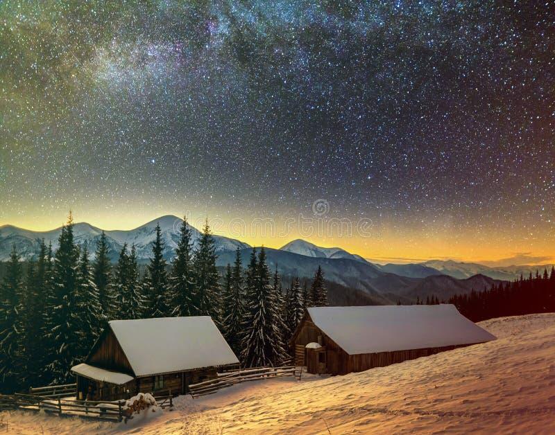 Stary drewniany dom, buda i stajnia, stos łupka w głębokim śniegu na halnej dolinie, świerkowy las, odrewniali wzgórza na ciemnym obraz stock