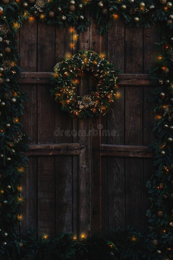 Stary drewniany drzwi dekorujący z i z ciepłymi światłami Bożenarodzeniową girlandą i wiankiem, fotografia royalty free