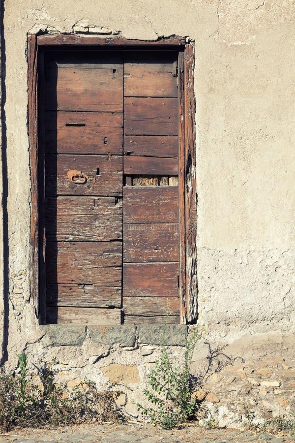 Stary drewniany drzwi na kamiennej ścianie dom obrazy royalty free
