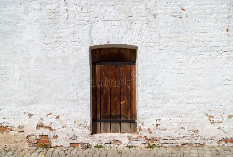 Stary drewniany drzwi w białej ścianie z cegieł zdjęcia royalty free