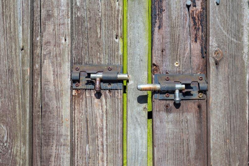 Stary drewniany drzwi z dwa rdzewiał kruszcowych kędziorki fotografia royalty free