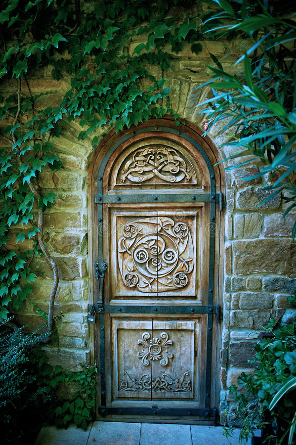 Stary drewniany drzwi z rzeźbiącym wzorem w tajemniczym ogródzie zdjęcia stock