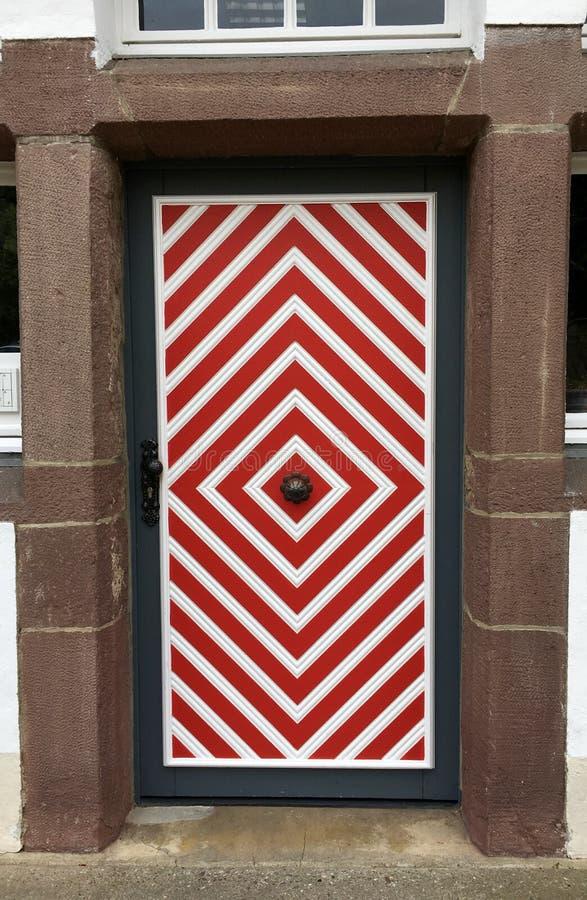 Stary drewniany dzwi wejściowy z czerwoną i białą farbą fotografia stock