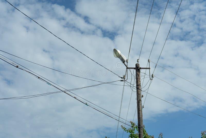 Stary drewniany elektryczny słup z lampą obłoczny niebo i wiele kablami która biegają w różnych kierunkach, zdjęcie royalty free