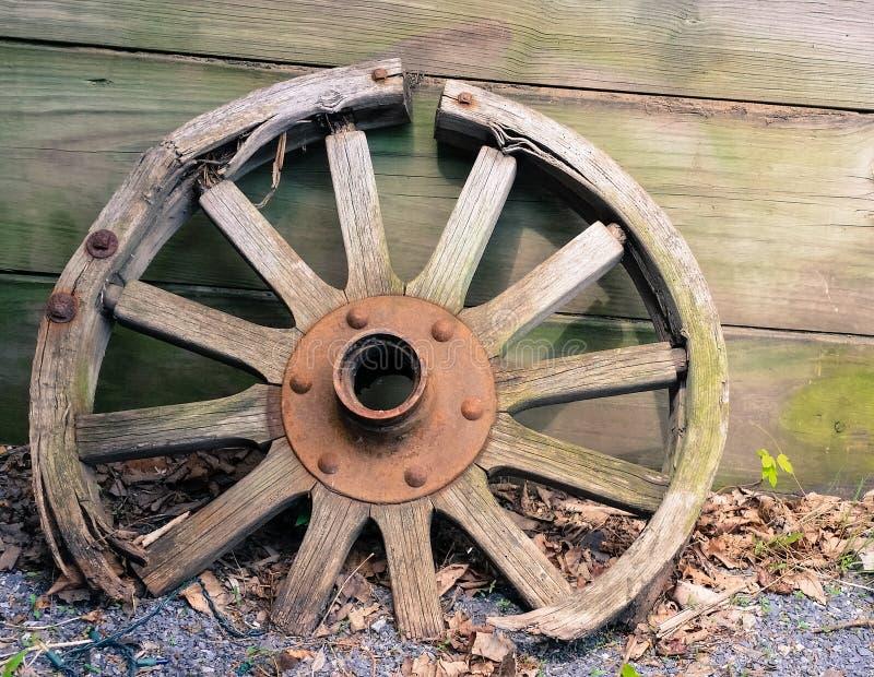 Stary drewniany furgonu koło opiera przeciw ścianie obraz royalty free