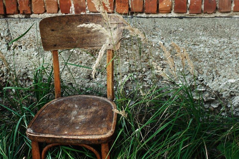Stary drewniany krzesło i trawa w podwórku na tle starzejący się hou obrazy royalty free