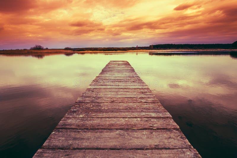 Stary Drewniany molo, Spokojna rzeka Przy Kolorowym zmierzchu wschodem słońca fotografia royalty free