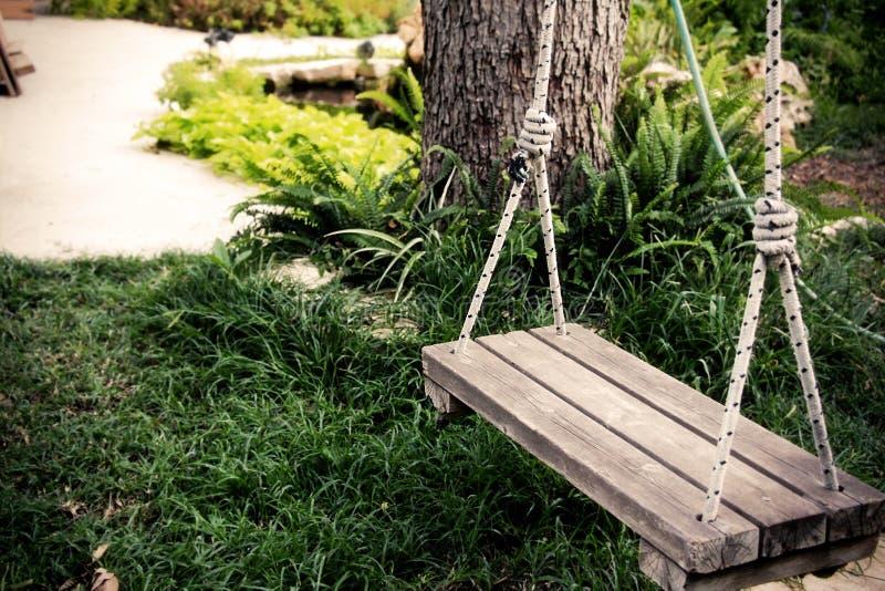 Stary drewniany rocznik huśtawki obwieszenie od wielkiego drzewa w ogródzie zdjęcia royalty free