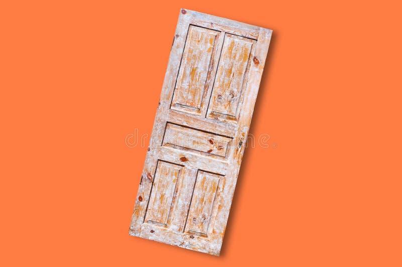 Stary drewniany unpainted drzwi w centrum na pomarańczowym tle fotografia royalty free
