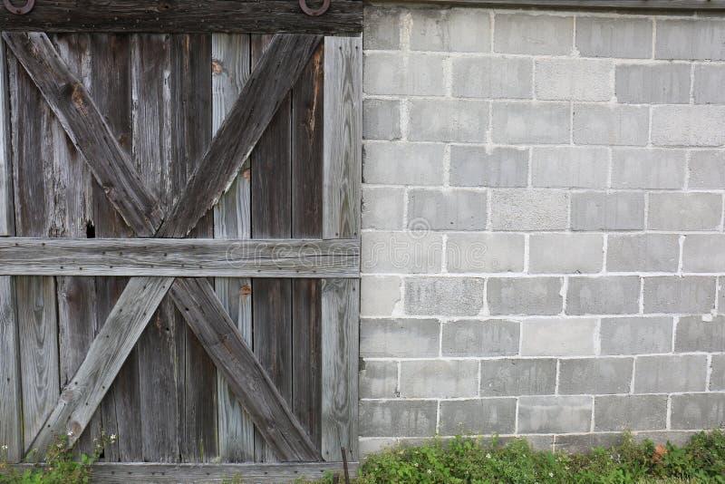 Stary drewno Wietrzejący stajni drzwi z cementu bloku ścianą obraz stock