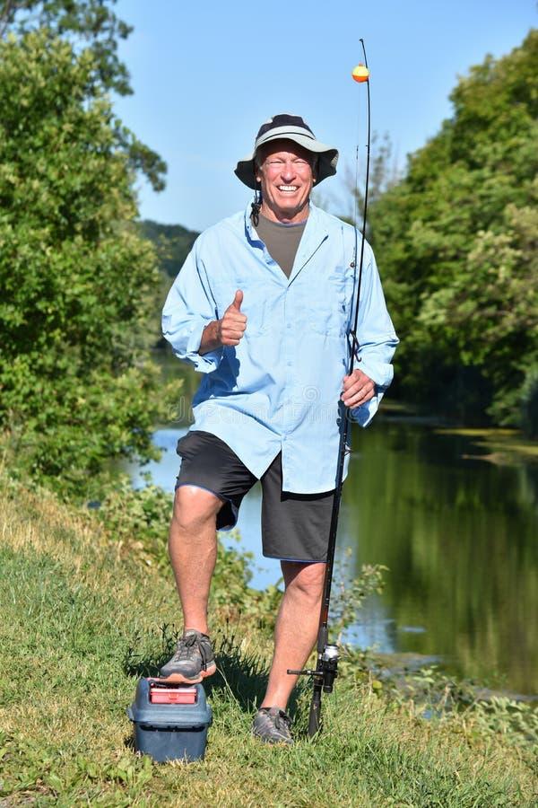 Stary emeryt Dorosłej samiec rybak Z aprobatami Z Rod Outdoors I rolką fotografia royalty free