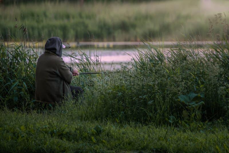 Stary fisher z prąciem blisko wody fotografia stock