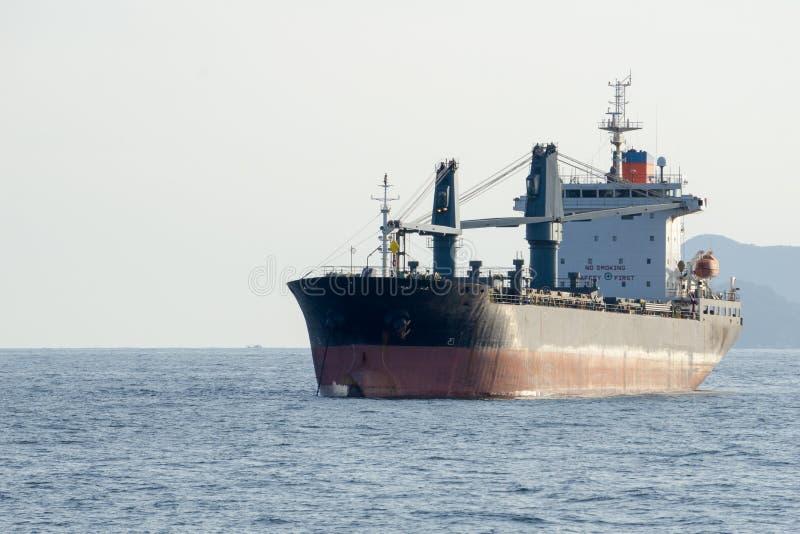 Stary handlowy ładunku statek z ciężkimi żurawiami zakotwicza w morzu obraz royalty free
