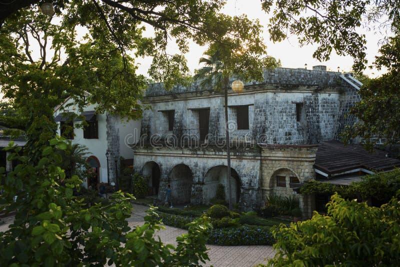 Stary historyczny domowy widok przez tropikalnych rośliien Fortu San Pedro widok w zmierzchu Stary dziejowy fort w Filipiny zdjęcia royalty free