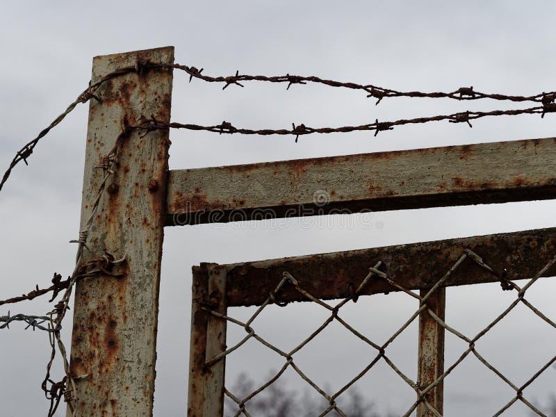 Stary i o?niedzia?y ogrodzenie ochronne i drzwi z drutem kolczastym na wierzcho?ku obrazy royalty free