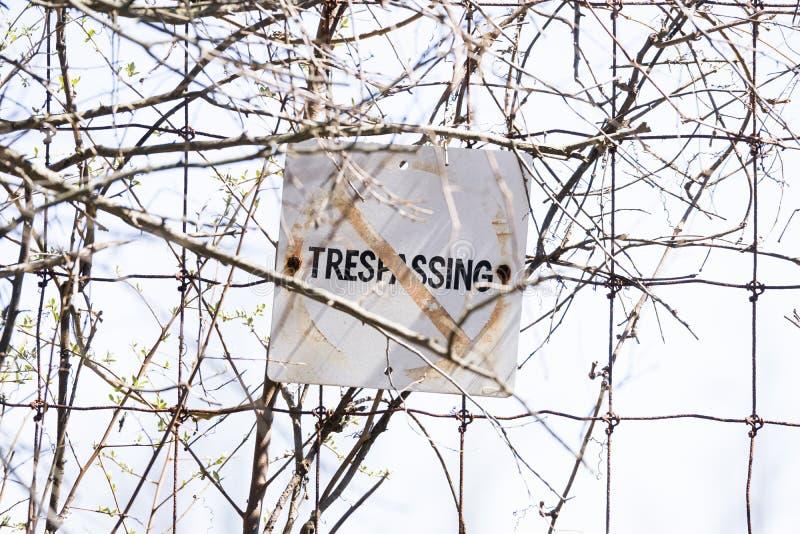 Stary i wietrzejący Żadny trespassing znak wysyłał druciany ogrodzenie, skrytka fotografia royalty free