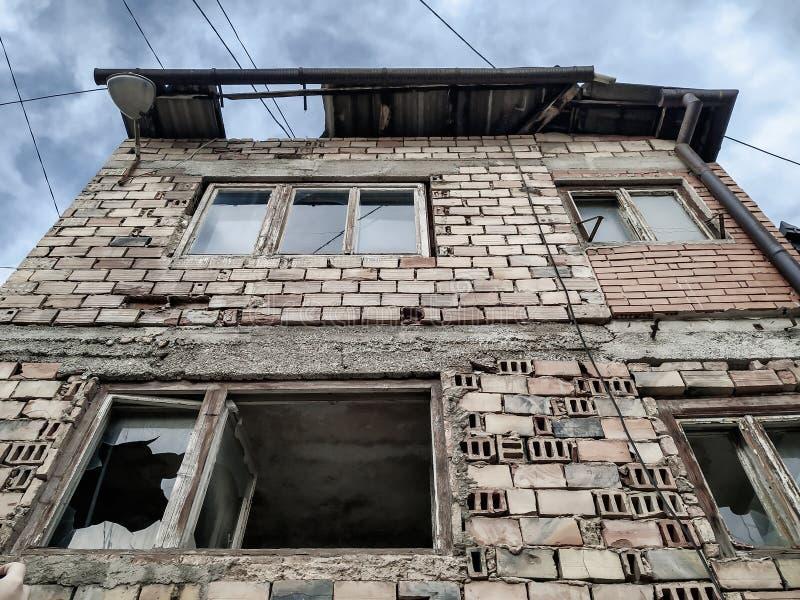Stary i zniszczony opuszczony dom z rozbitymi szklanymi oknami i zniszczonymi czerwonymi cegłami, całkowicie zniszczony i uderzon zdjęcia royalty free