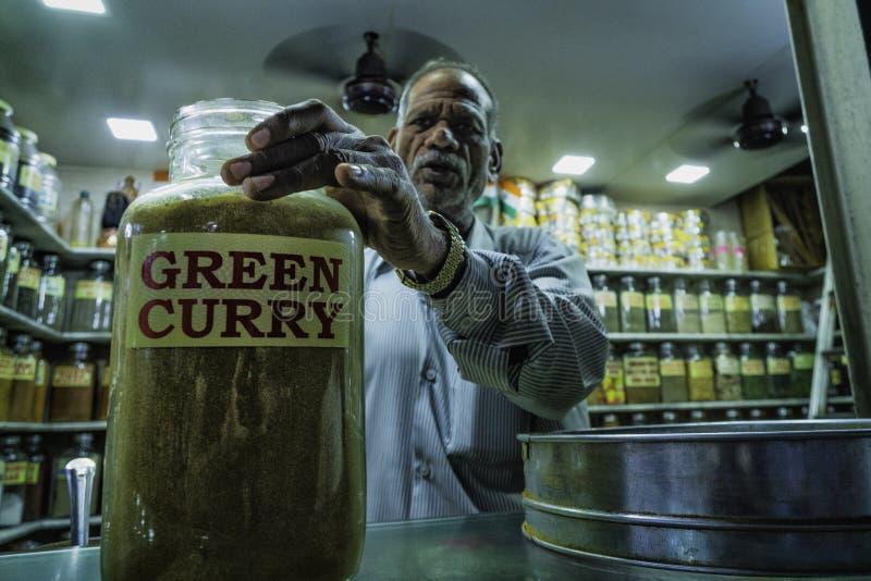 Stary indyjski mężczyzna z dużym szklanym słojem gorący curry obraz stock