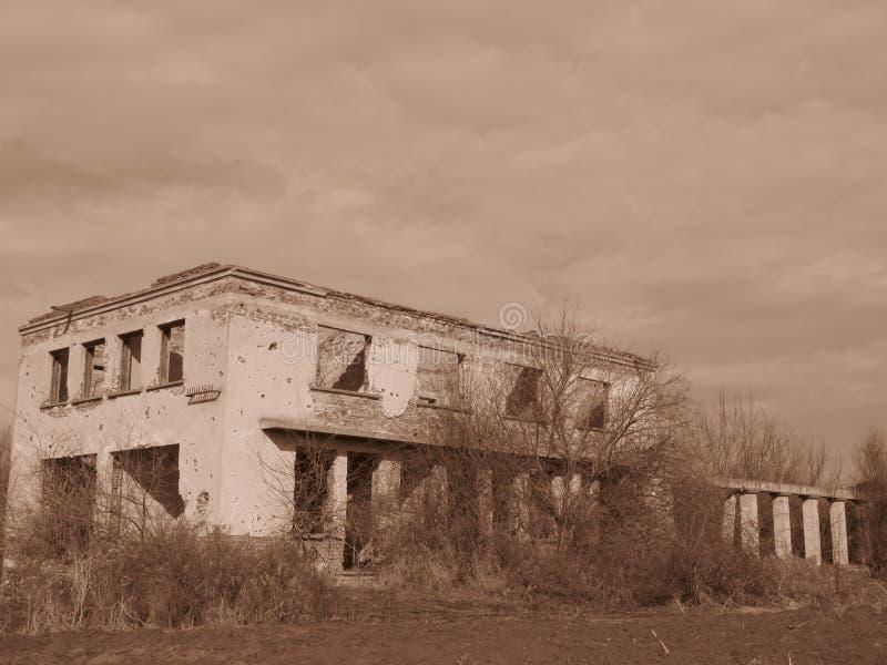 Stary isoleted wyburzający zaniechany budynek przerastający z krzakami i krzakami w Sepiowym colour fotografia stock