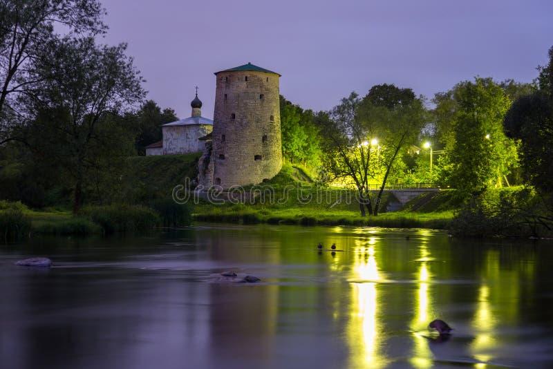 Stary kamienia wierza średniowieczny forteca i mały kościół odbija w rzece przy nocą Pskov fortyfikacje, Rosja zdjęcia stock