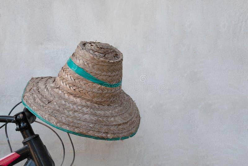 Stary kapelusz wyplatający rolnik na czarnym bicyklu zdjęcie royalty free