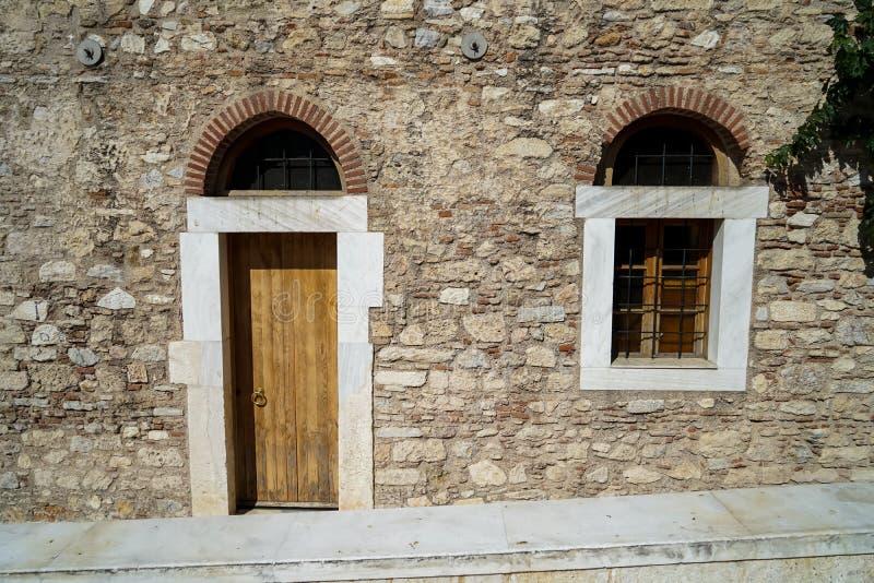 Stary klasyczny mały kościół łuku drzwi i nadokienna rama na ziemskiego brzmienia kamiennej ściany naturalnym fasadowym tle z mar obrazy stock