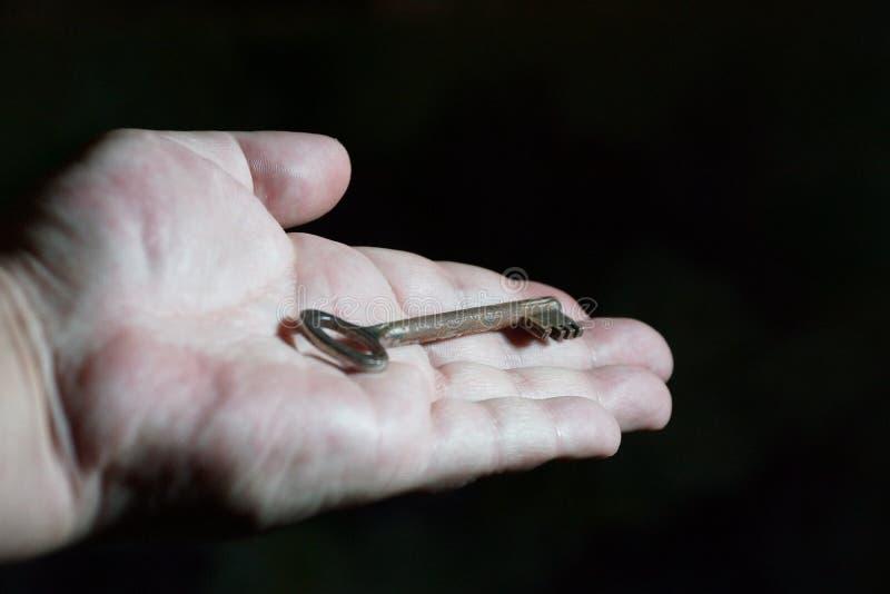 Stary klucz w mężczyzna ręce na czarnym tle na kumpel i zdjęcia royalty free