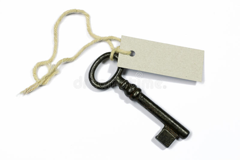 Stary klucz z pustą etykietką na bielu obraz stock